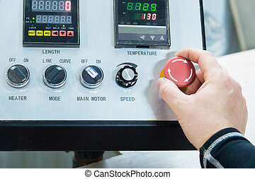 Close-up of a man's hand on a red button on the control panel. Emergency stop or start of equipment and production