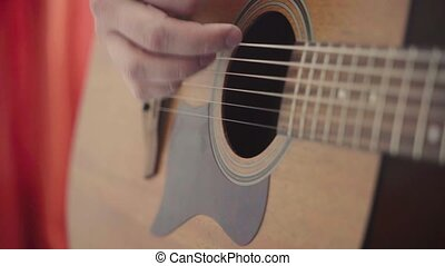 Close-up of a man's hands playing the guitar.