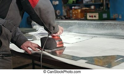 Close-up of a manual sander controlled by a worker at the factory and sanding a metal part