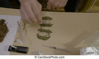 Close up of a marijuana addicted man separating the weed...
