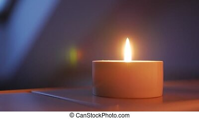 Close-up of blow out a candle against a wall background, shallow depth of field with focus on the wick and flame.