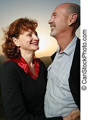 Close-up of a mature couple embracing outdoors at sunset.
