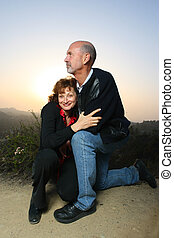 Close-up of a mature couple embracing outdoors at sunset.