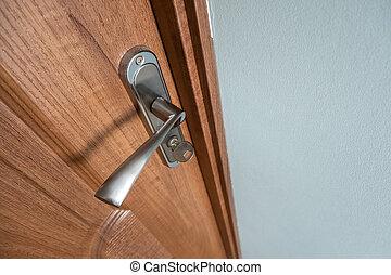 Close up of a metal door handle on wooden doors.