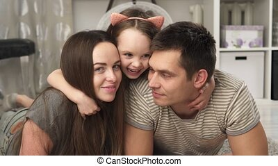 mother, father and little daughter smiling