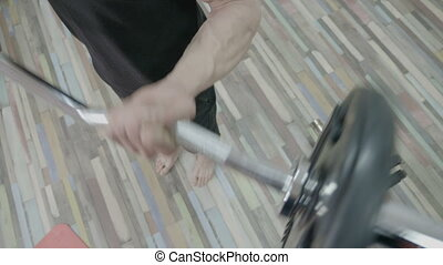 Close up of a muscle man working out his arms in a cross fit gym by lifting dumbbells