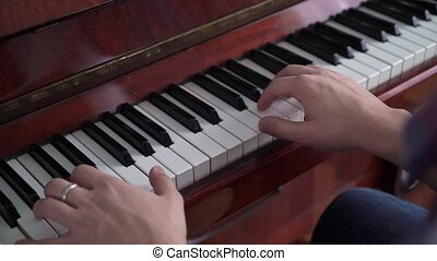 Close-up of a music performer's hand playing the piano.