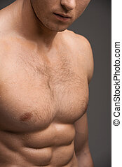 Close up of a nude man muscular chest. Standing isolated over grey background