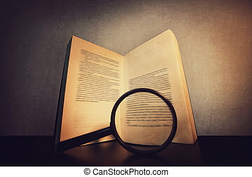 Close up of a open book on the table and a magnifying glass searching through the pages text. Old textbook sheets isolated on dark grey background. Education symbol, in search of knowledge concept.