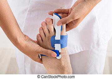 Orthopedist Fixing Plaster On Injured Man's Foot