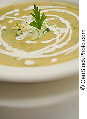 Close-up of a parsley leaf garnish on a zucchini and carrot cream soup