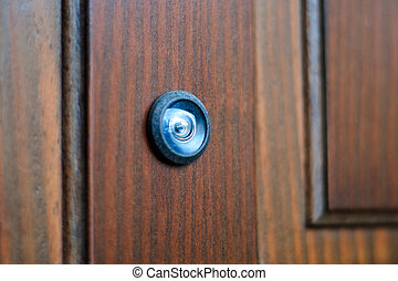 close-up of a peephole on a wooden door