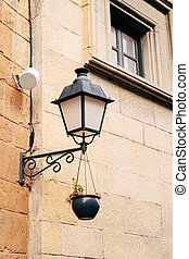 Close-up of a pendant street lamp on a bracket by a window with a flower pot on a chain.