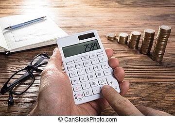 Person Calculating Profit On Calculator