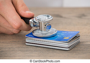 Person Hand Holding Medical Stethoscope On Credit Card Stack