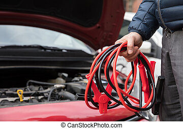 Close-up Of A Person Holding Jumper Cables