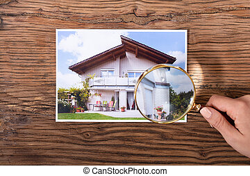 Person Holding Magnifying Glass Over The House Photograph