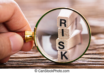 Person Inspecting Risk Block With Magnifying Glass