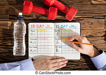 Person Making Exercise Plan On Notebook