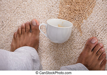 Person's Feet Standing Near Spilled Coffee - Close-up Of A...