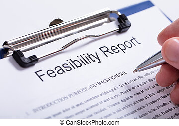 Person's Finger Holding Pen Over Feasibility Report