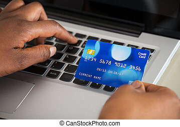 Person's Hand Using Debit Card While Shopping Online -...