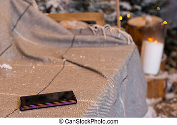 Close up of a phone in a swing with a blanket in a snow-covered park