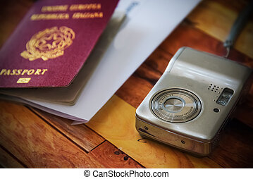Close up of a photo camera with a passport on the background