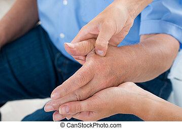 Physiotherapist Massaging Palm Of A Man