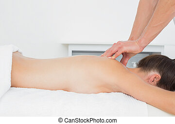 Close-up of a physiotherapist massaging woman's back