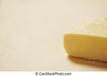 Close-up of a piece of butter is on the rolled raw dough