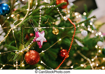 Close-up of a pink Christmas tree toy in the shape of a star on the branches of a Christmas tree.