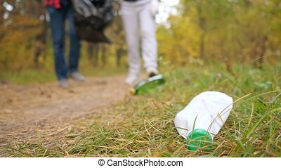 Close-up of a plastic bottle in the grass against the background of a couple collecting garbage in the forest