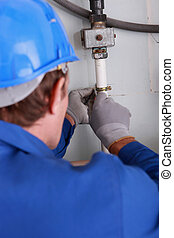 Close up of a plumber fixing some internal water pipes