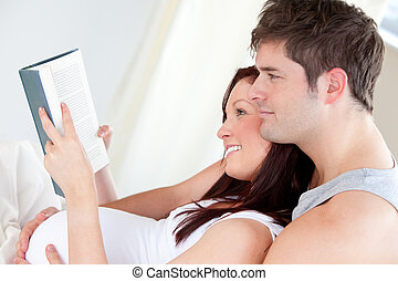 Close-up of a pregnant woman and her husband reading a book on the sofa at home
