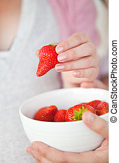 Close-up of a pregnant woman eating a bowl of strawberries