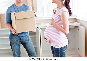 Close-up of a pregnant woman talking to her husband who is holding a cardboard in their new house