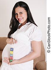 Close up of a pregnant woman with baby letters on her hand