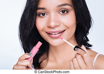 Close up of a pretty woman applying lip gloss