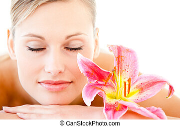 Close-up of a pretty woman lying on a massage table with a flower in a health spa