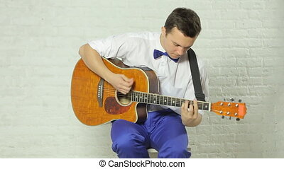 Close-up of a professional guitar playing in the studio on a white background