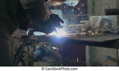 Close up of a professional woman blacksmith using welding...