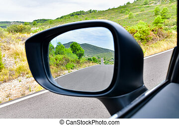 Close up of a rear view mirror with an empty road with mountains at the back