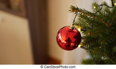 Close-up of a red glossy Christmas ball on the branches of a real Christmas tree.