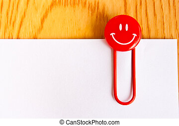 close up of a  red paper clip and white paper on wood table