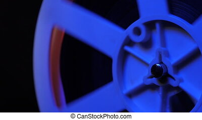 Close-up of a reel. Old 8mm film projector showing film at night in dark room with blue light. Vintage retro objects, cinematograph concept