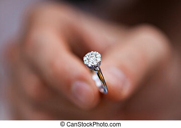 Close-up of a ring in a mans hand. young man giving engagement ring to his girlfriend. Man making marriage proposal to his beloved woman. Romantic date.