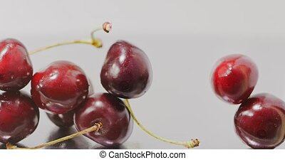 Close-up of a ripe red large cherries slowly falls and fills the screen. Slow motion. Berries background. Full HD video, 240fps,1080p