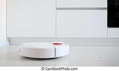 Close-up of a robot vacuum cleaner picking up trash from the floor, side view