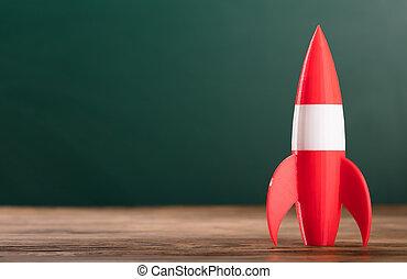 Close-up Of A Rocket On Wooden Desk